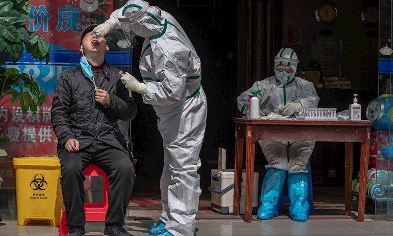 Un trabajador médico con equipo de protección completo realiza una prueba a un hombre para detectar síntomas de COVID-19 en una calle de Wuhan.