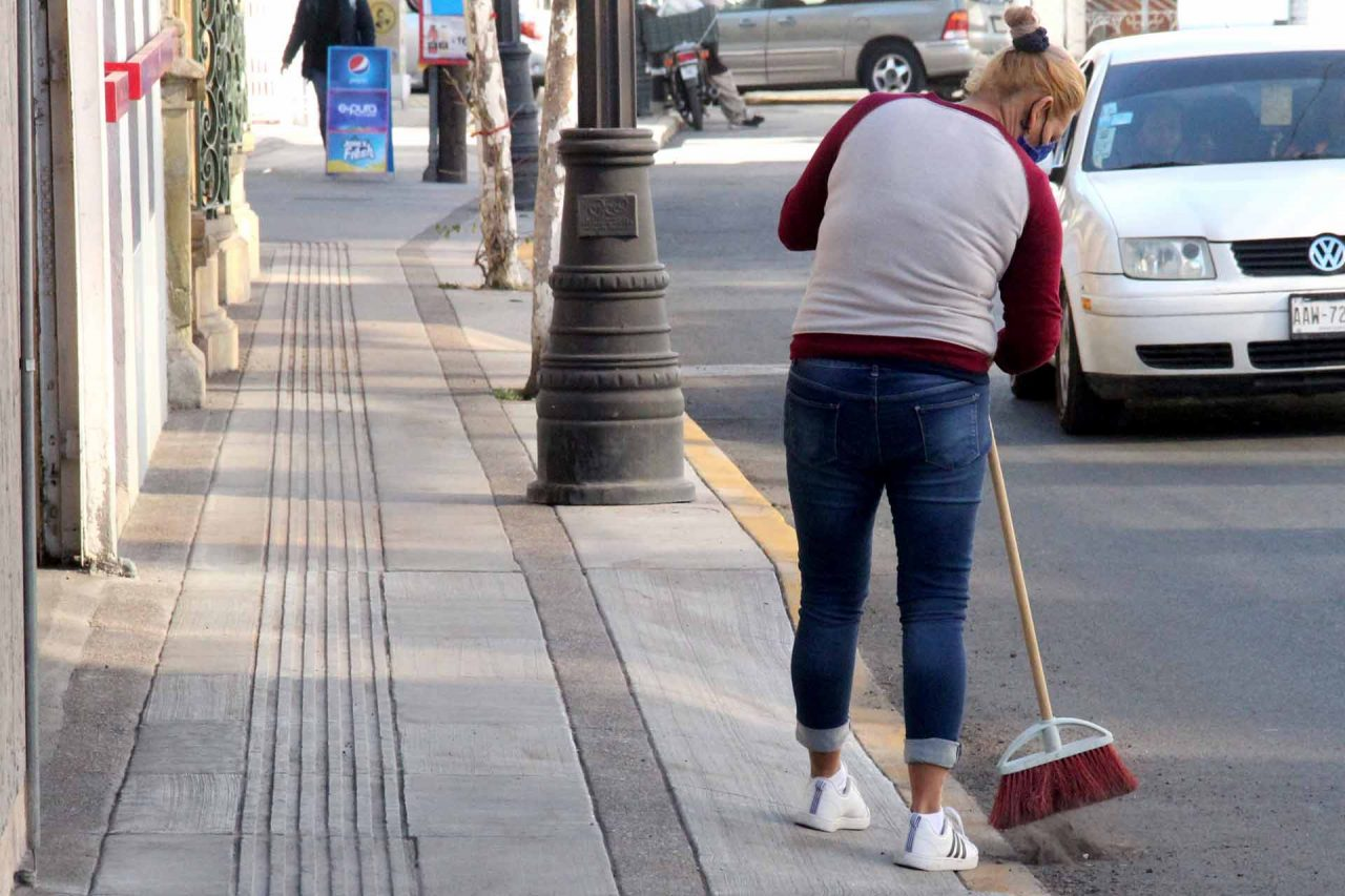 Empleada doméstica barriendo la calle
